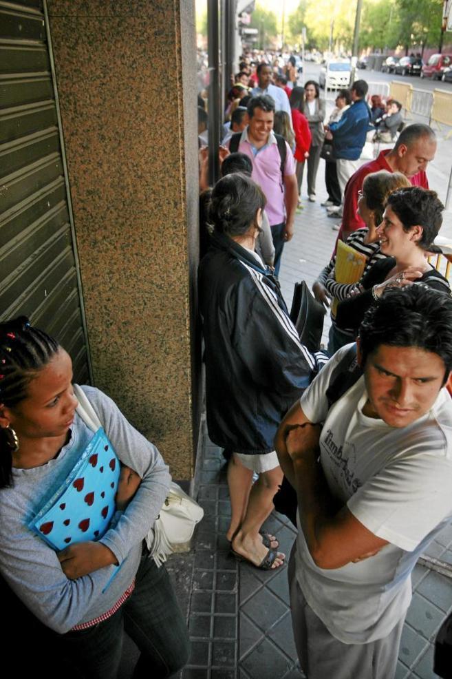 Ciudadanos hacen cola en la puerta del Registro Civil de Madrid.