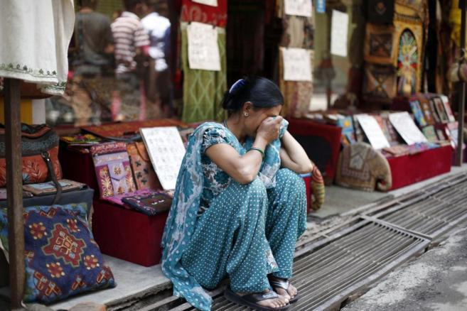na mujer llora sentada al aire libre en Sankhu, a las afueras de...