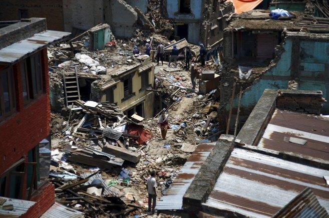 Ciudadanos nepalíes caminan entre casas en ruinas tras un nuevo...