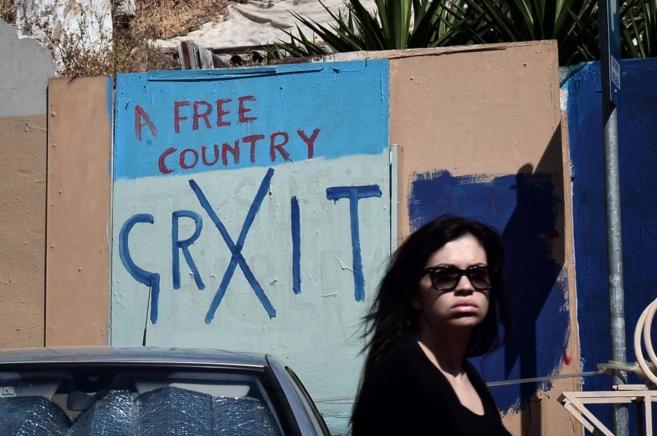 Una mujer pasa frente a una pintada con el lema 'Grexit' en...