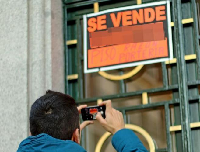 Un joven fotografía un cartel de 'Se vende' en la entrada a...