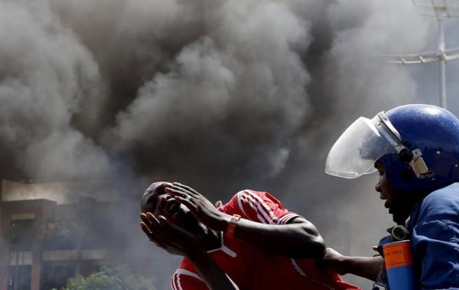 Un detenido se lamenta ante una barricada ardiendo en Bujumbura.