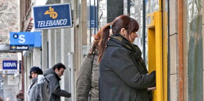 Una mujer saca dinero de un cajero en una calle con varias sucursales...
