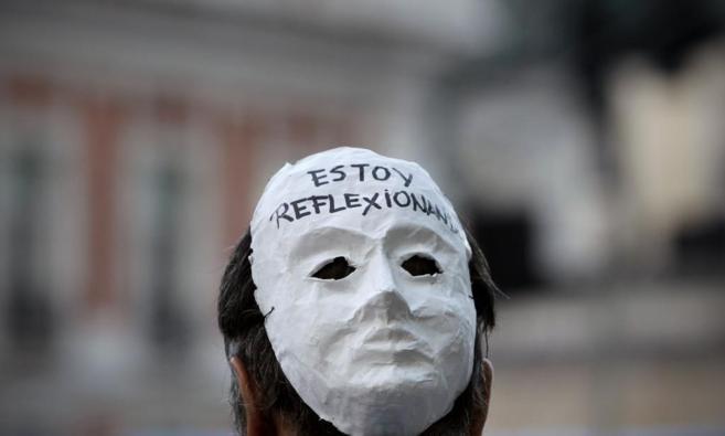 Uno de los manifestantes del 15-M luce un mensaje en su careta durante...