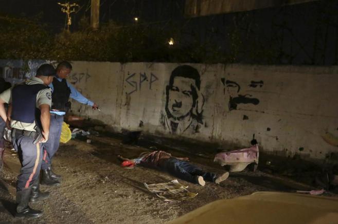 Oficiales de policía observan el cadáver de un compañero abatido en...