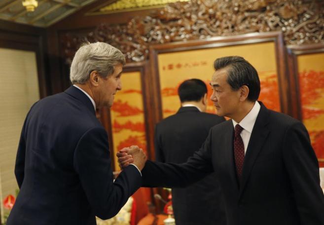 El secretario de Estado John Kerry saluda a su homólogo Wang Yi, hoy,...