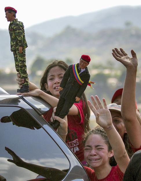 Partidarias de Maduro agitan muñecos de Chávez en los Teques.