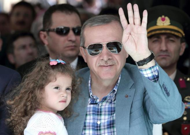 El presidente Erdogan, junto a una niña en un acto electoral.