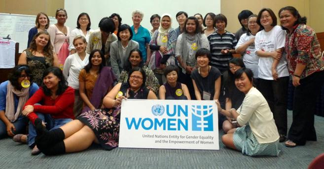 Un grupo de mujeres posan bajo un cartel con el logo de la...
