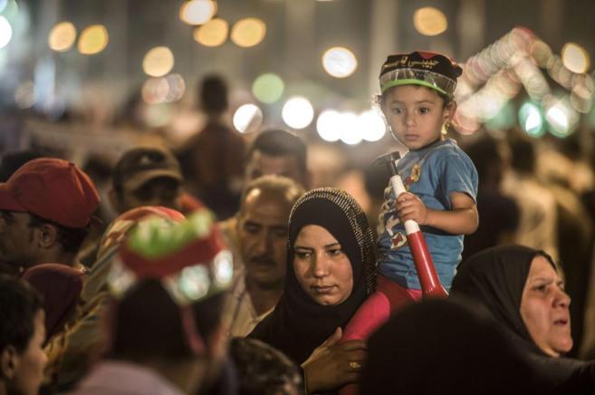 Una mujer lleva a su hijo en medio de una celebración sufí en las...