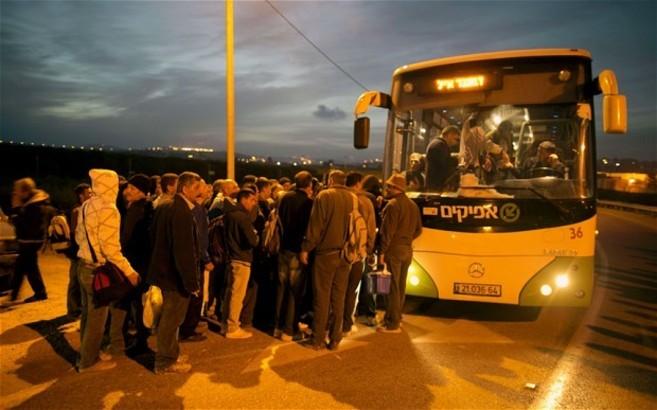 Trabajadores palestinos cogen el autobús para ir a trabajar a...