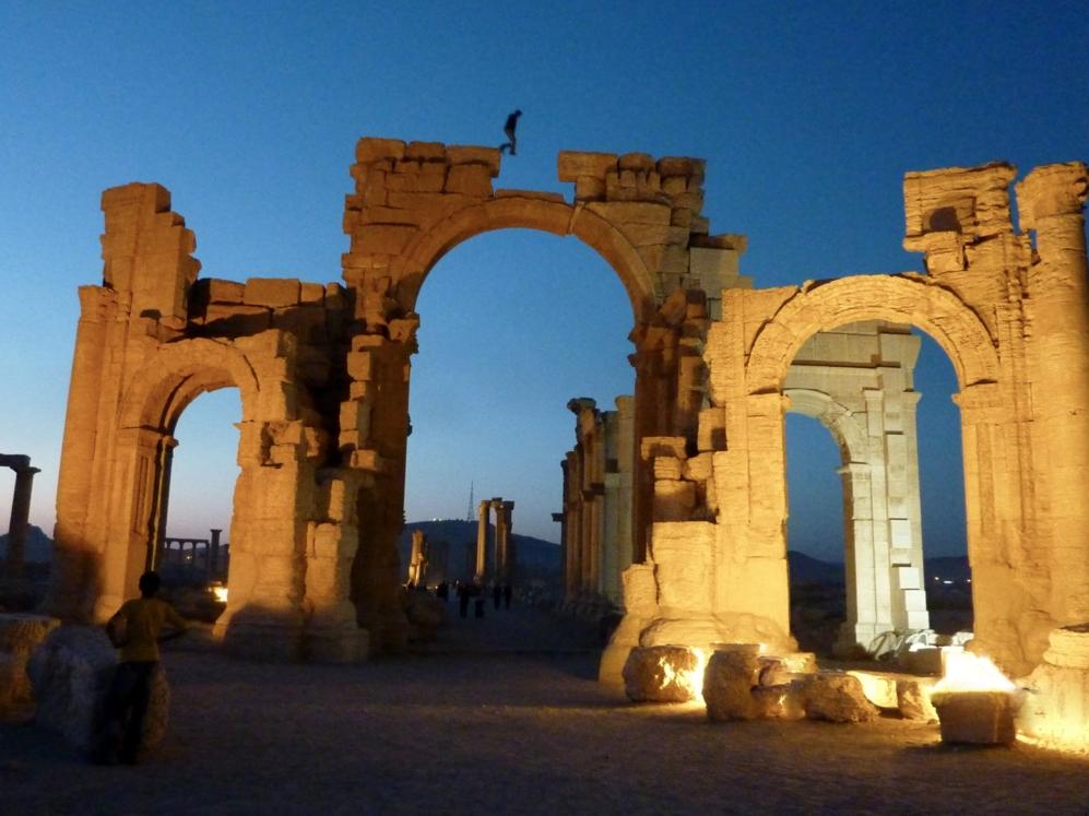 Un adolescente juega sobre el arco de entrada a Palmira.