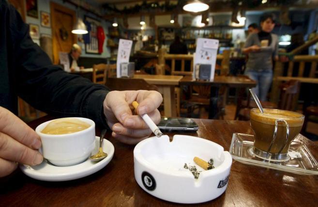 Un hombre fuma en una cafetería.