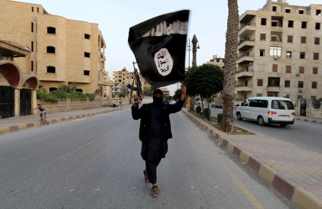 Un miliciano del actualmente autoproclamado Estado Islámico ondea su...