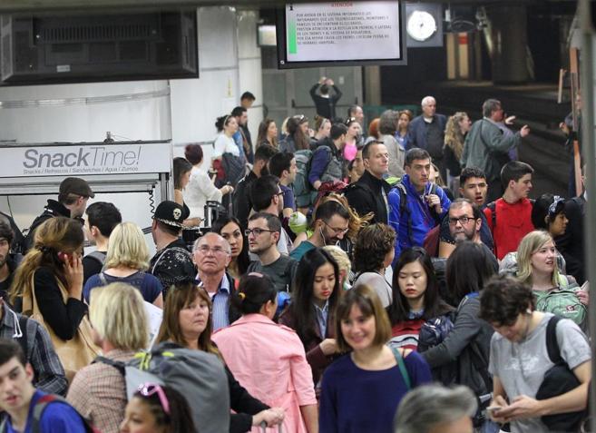 Viajeros apostados en los andenes de la estación de Sants en plena...