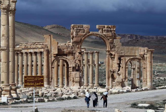 Un grupo de sirios camina entre los restos arqueológicos de Palmira.