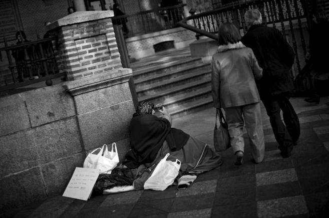 Una mujer indigente pide limosna en la puerta de una iglesia en el...