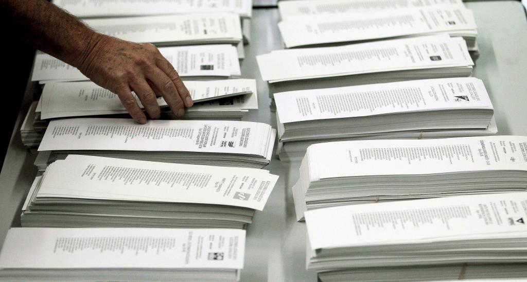 Un ciudadano coge una papeleta de una cabina en un colegio electoral...