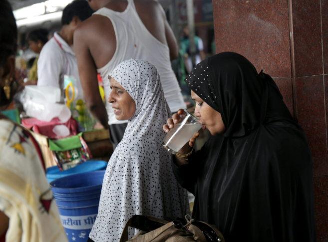 Una mujer bebe un vaso de agua de cal en Calcuta (India) por la ola de...