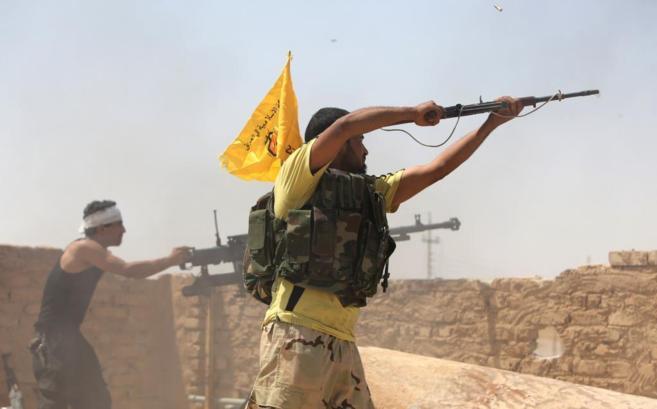 Milicianos chiíes iraquíes disparan contra IS en Baji, cerca de...