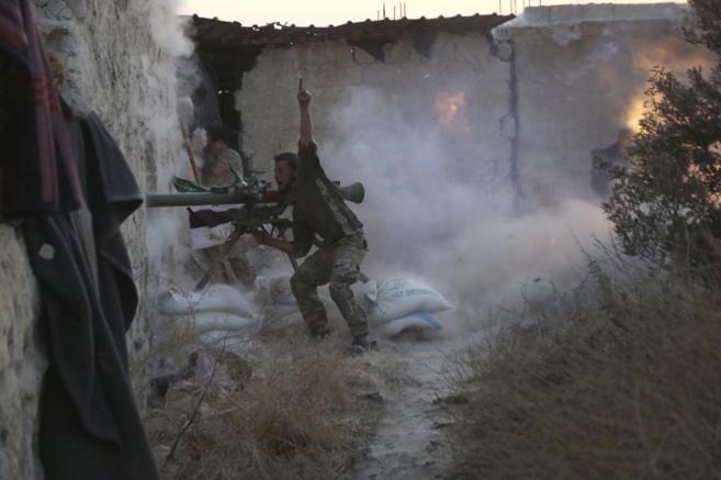 Un rebede dispara a las fuerzas de Asad durante los combates en...