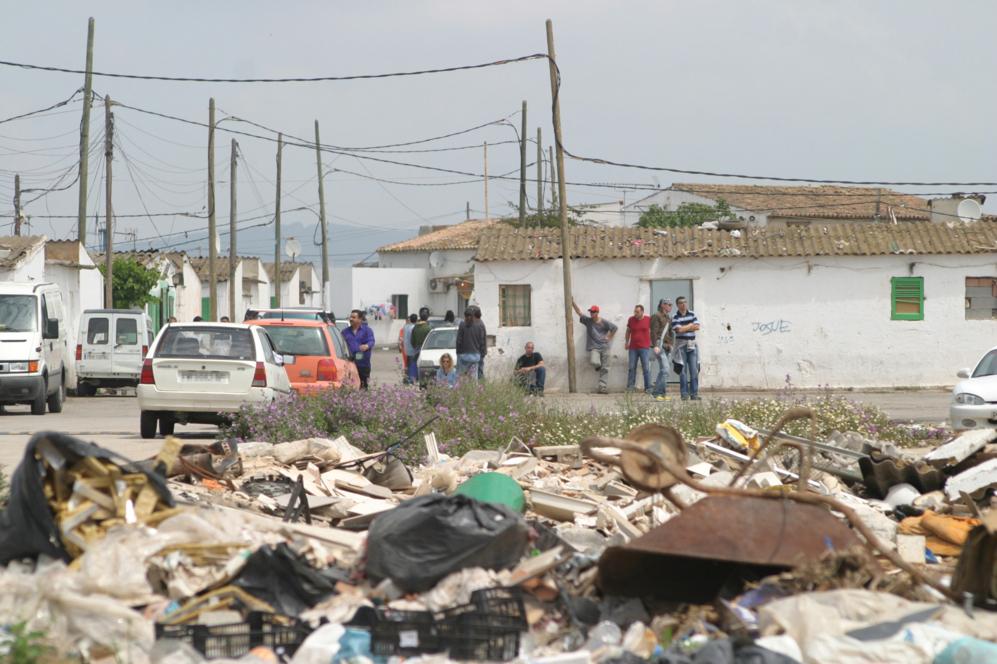 Vecinos de Son Banya junto a algunas de las viviendas del poblado y...