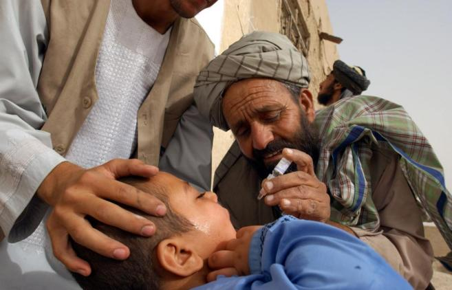 Un trabajador de UNICEF poniendo una vacuna contra la polio a un niño...