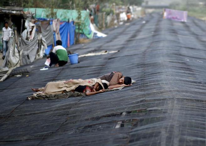 Unos hombres duermen en la calle mientras la ola de calor que azota a...