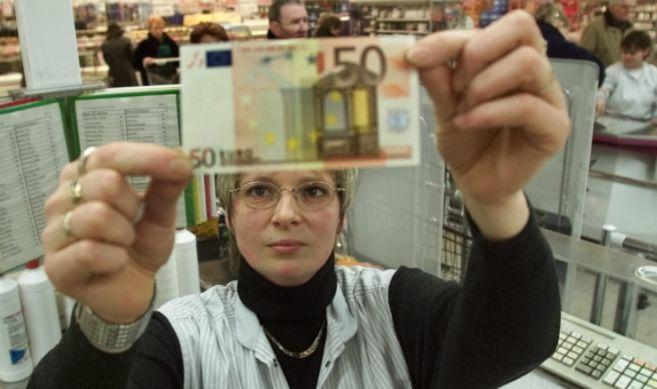 Una cajera alemana con un billete de 50 euros.