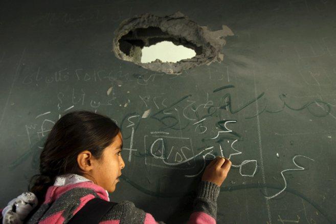 Una niña palestina escribe en una pizarra dañada por uno de los...