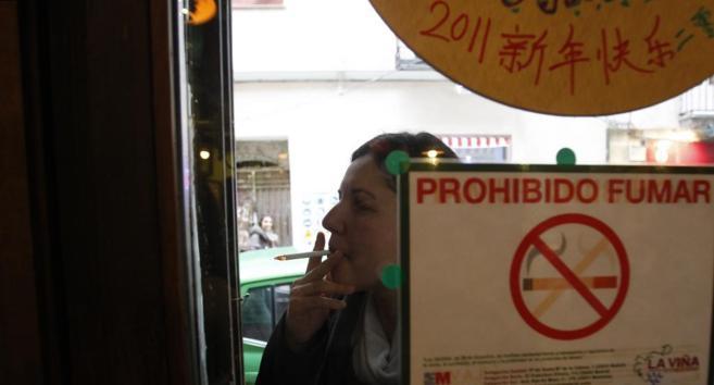 Una mujer fumando a la entrada de un bar.