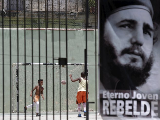 Niños juegan en un parque junto a una imagen del ex presidente cubano...
