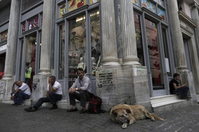 Atenienses descansan en el escalón de una tienda en la calle Ermou en...