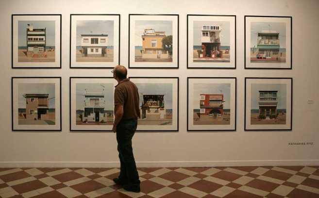 Un espectador admira la serie de fotografías sobre las casas de...