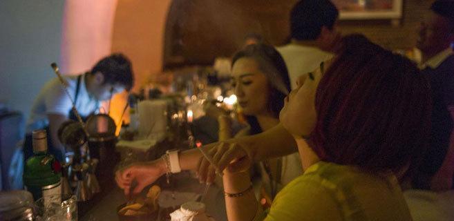 Una mujer fuma en un bar de Pekín