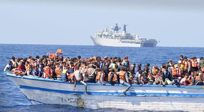 Cientos de inmigrantes viajan en una embarcación, en las costas de...
