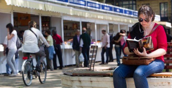 Unos lectores leen libros en la feria del libro de Bilbao