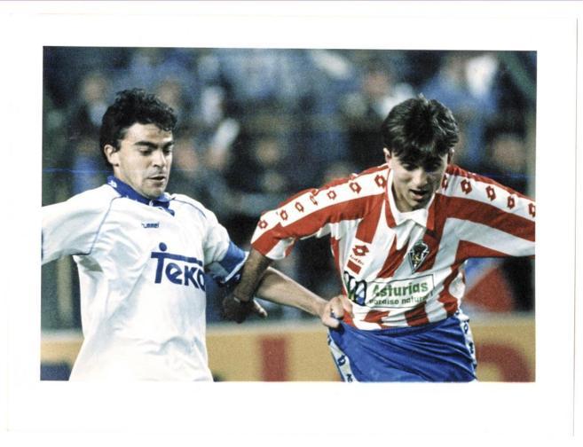 Juanele, con camiseta del Sporting, disputando un balón a Sanchís.