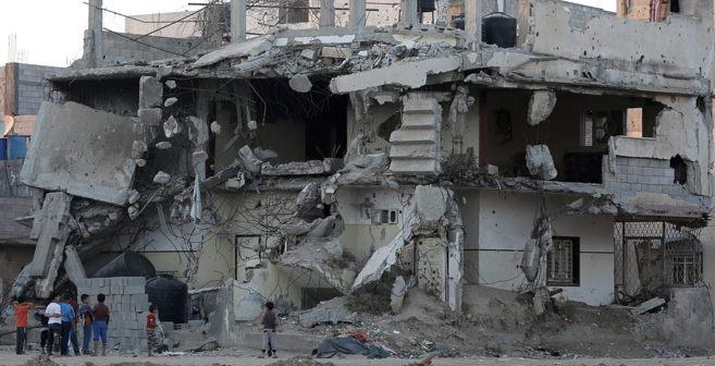 Niños palestinos juegan cerca de un edificio destruido durante el...