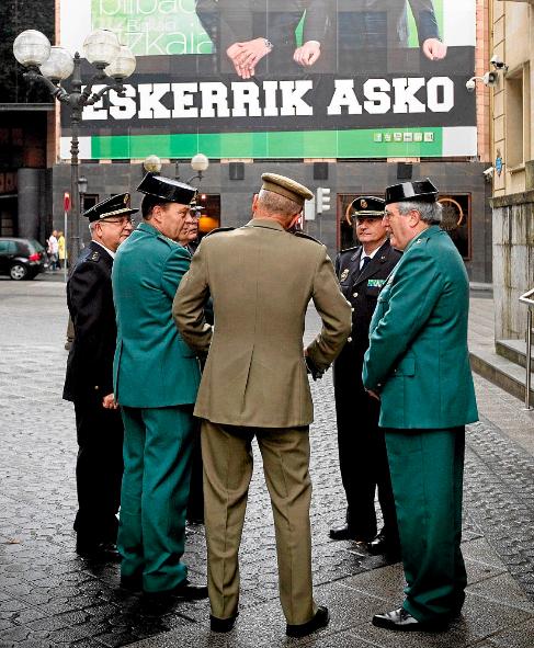 Policías, guardias civiles y militares, junto a un gran cartel que...