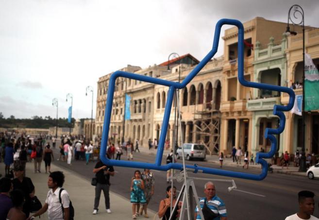 Decenas de cubanos pasean por el Malecón de La Habana junto a la obra...