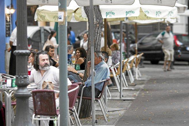 Varios usuarios disfrutan de una terraza en una calle de Valencia.