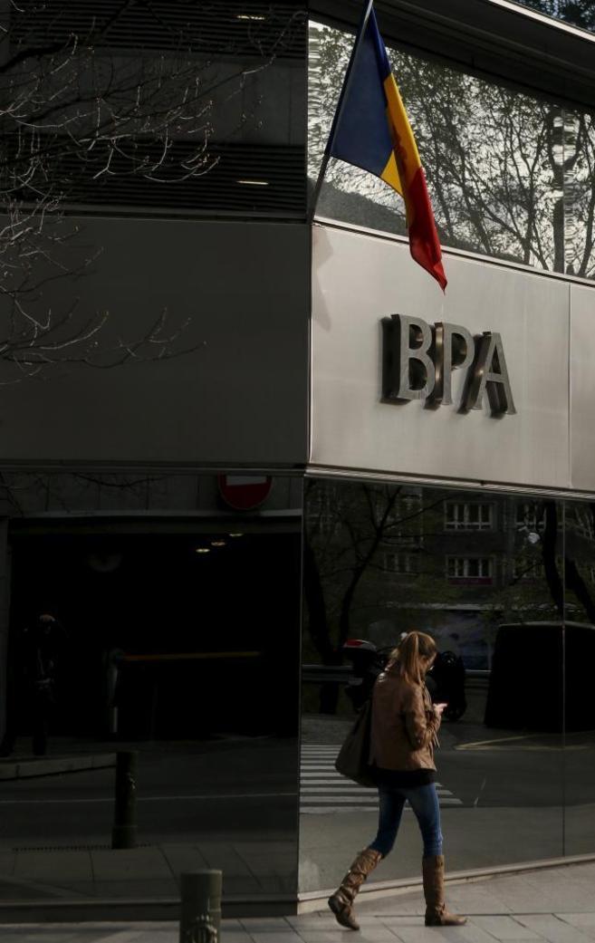 Una mujer camina ante una oficina de BPA en Andorra la Vella.