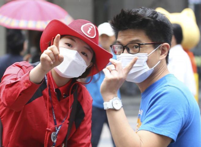 Una guía informa a un turista, ambos con mascarilla, en Seúl...