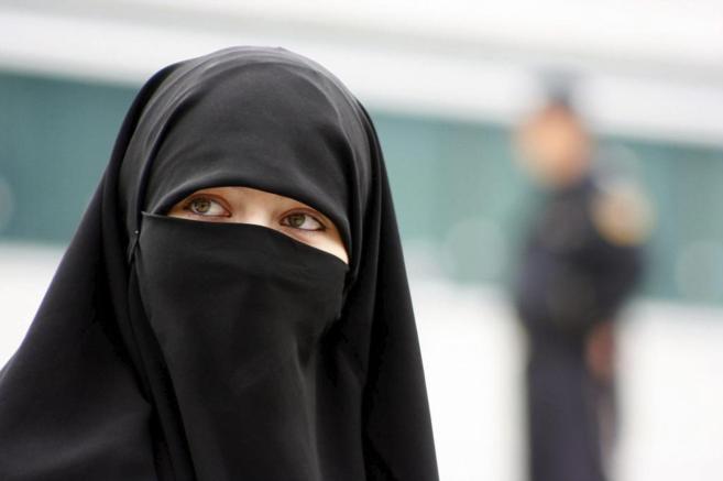 Una mujer bosnia musulmana, pasea por una calle de Sarajevo ataviada...