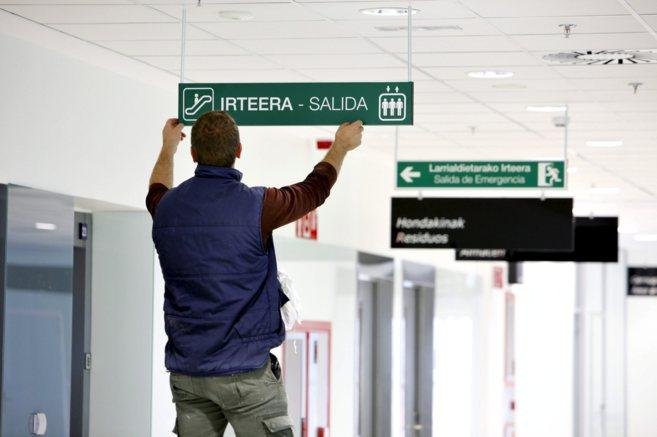 Un operario coloca carteles bilingües en un centro de salud en el...