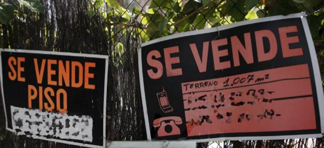Imagen de archivo de varios carteles anunciando un piso y un terreno...