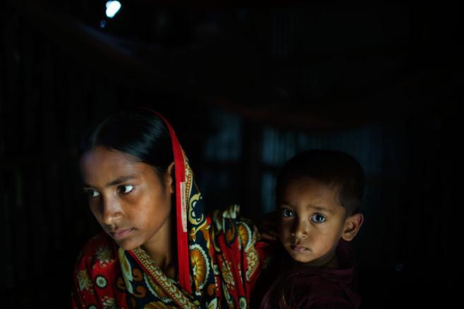La bangladesí Belkis, de 15 años, que se casó hace dos, sostiene a...