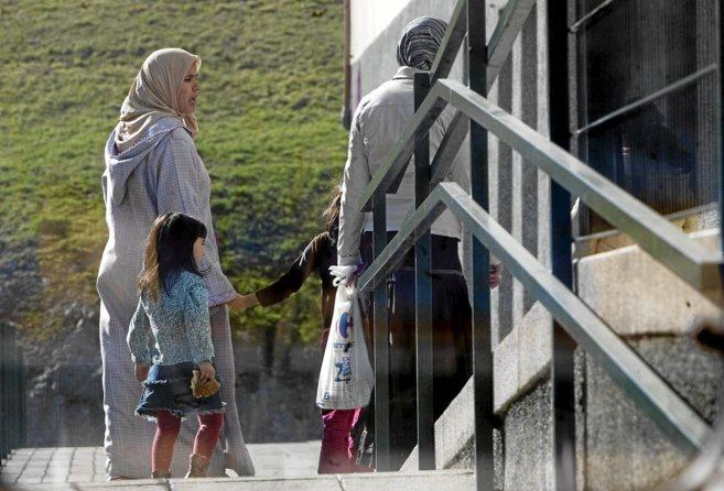 Niños inmigrantes entran a un colegio en Bilbao acompañados de sus...
