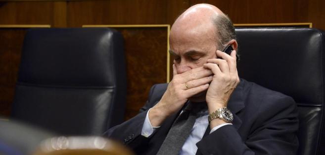 El ministro de Economía, Luis de Guindos, hablando por el móvil en...